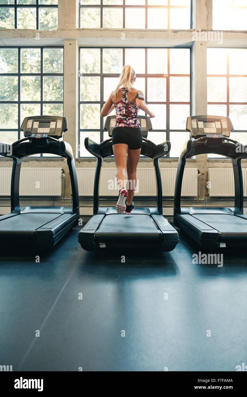 Vista posteriore del giovane femmina in esecuzione sul tapis roulant in palestra. Donna Fitness jogging al chiuso Immagini Stock