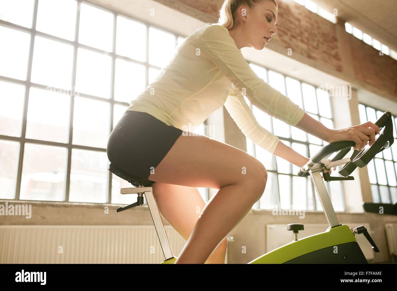 Vista laterale della donna fitness sulla bicicletta in palestra. Giovane atleta femminile la filatura su biciclette Foto Stock