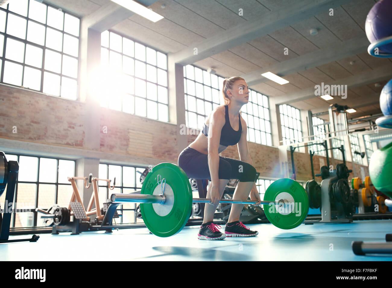 Giovane donna lavorando duro in palestra. Montare atleta femminile sollevamento pesi nel club salute. Foto Stock