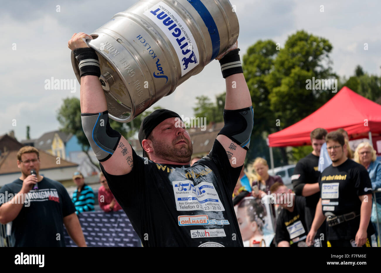 Un uomo forte dimostra la sua forza ad un pubblico di atletica leggera evento sportivo. Immagini Stock