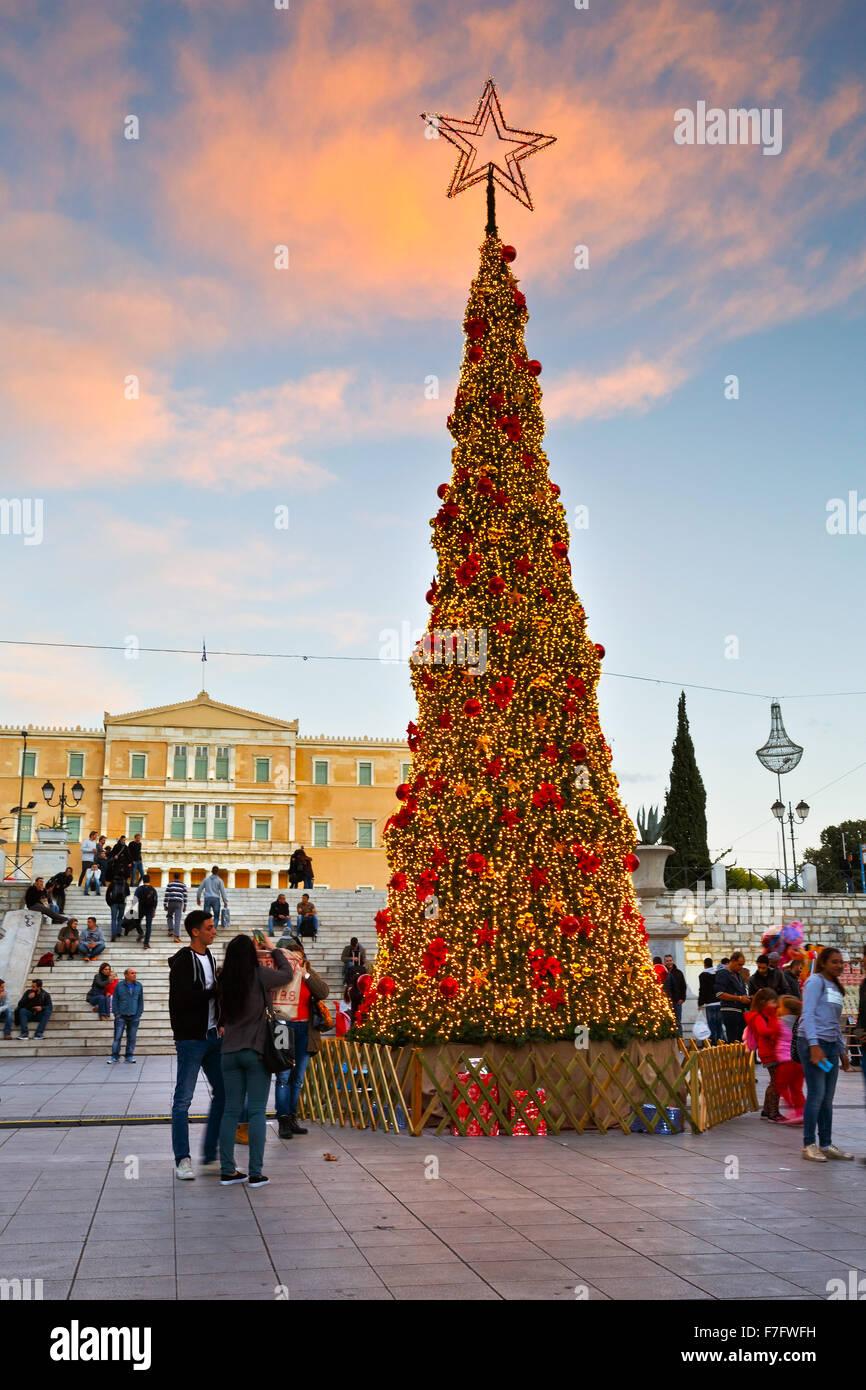 Le persone a un albero di natale davanti al parlamento greco in piazza Syntagma ad Atene durante l'avvento Immagini Stock