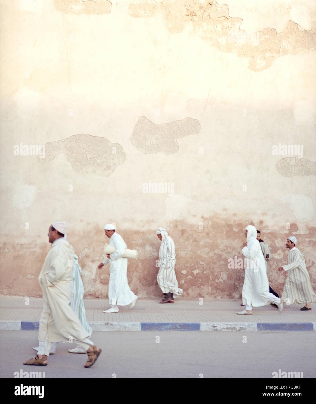 Marocchino uomini musulmani camminare velocemente oltre le mura della città sul loro modo di preghiere del Immagini Stock