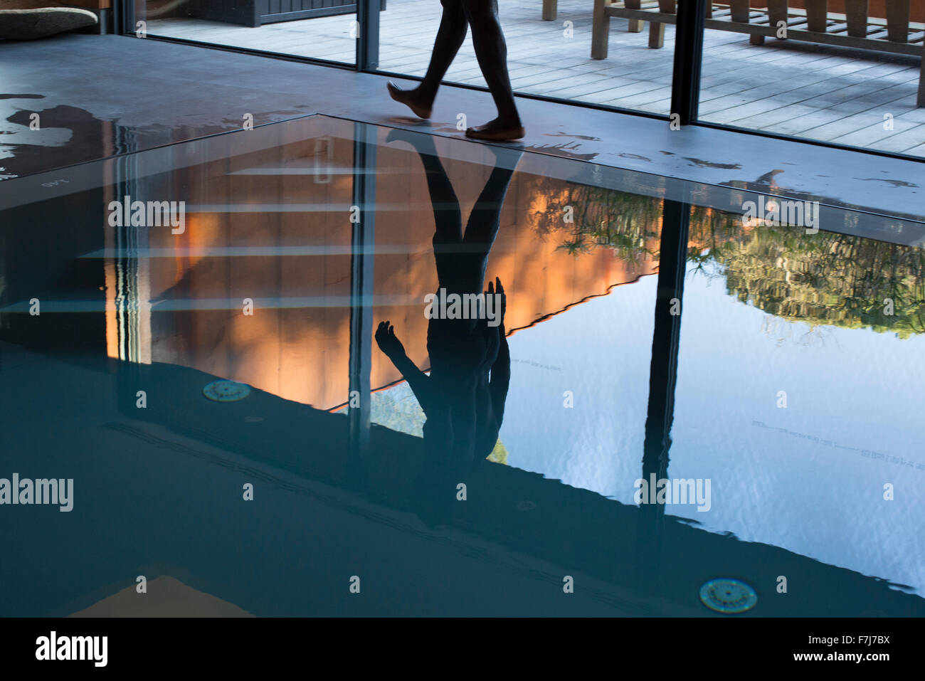 Uomo che cammina accanto alla piscina, riflette sull'acqua Immagini Stock