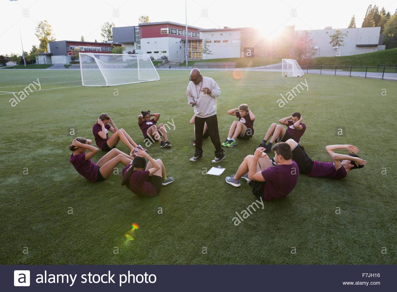 Alta scuola insegnante di educazione fisica studenti sit ups Immagini Stock