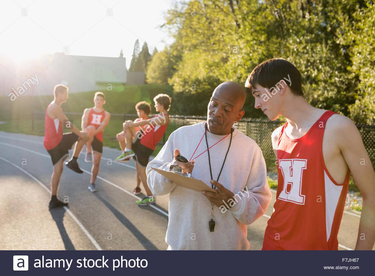 Fasatura dei pullman di alta scuola via e atleta di campo Immagini Stock