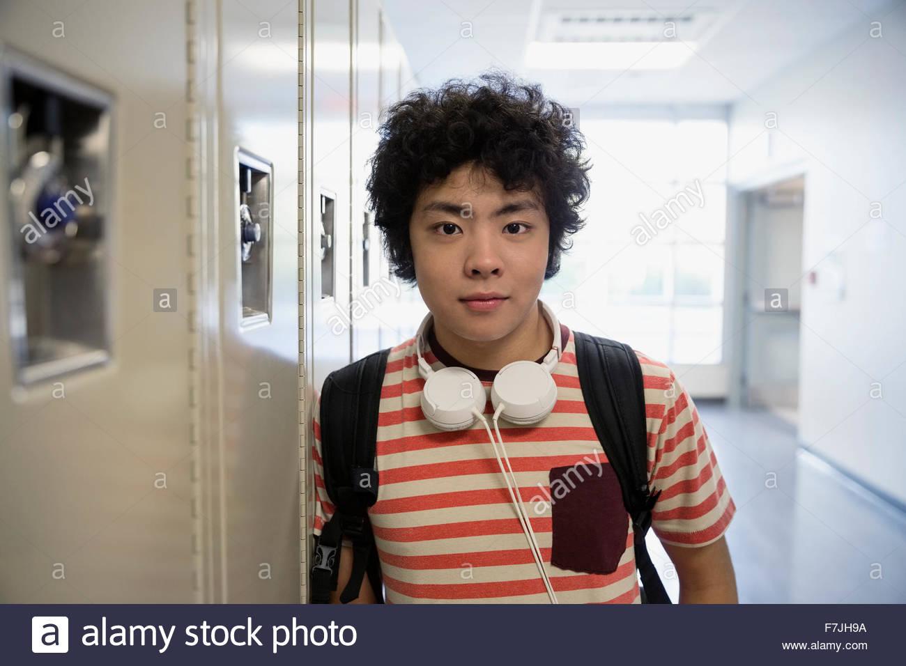 Ritratto fiducioso studente di scuola superiore con cuffie di armadietti Immagini Stock