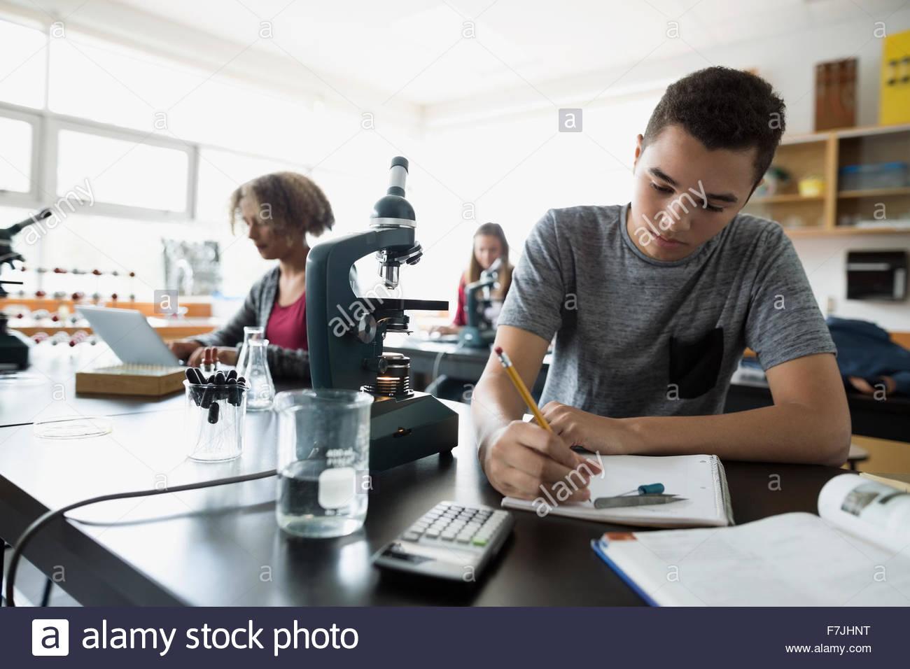 Studente di scuola superiore prendendo appunti science laboratory classroom Immagini Stock