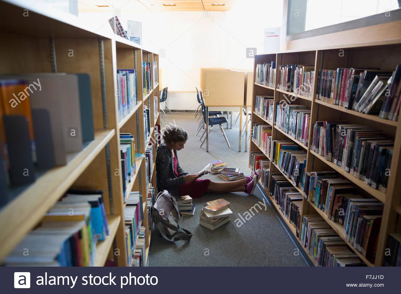 Alta scuola studente sul pavimento della libreria Foto Stock