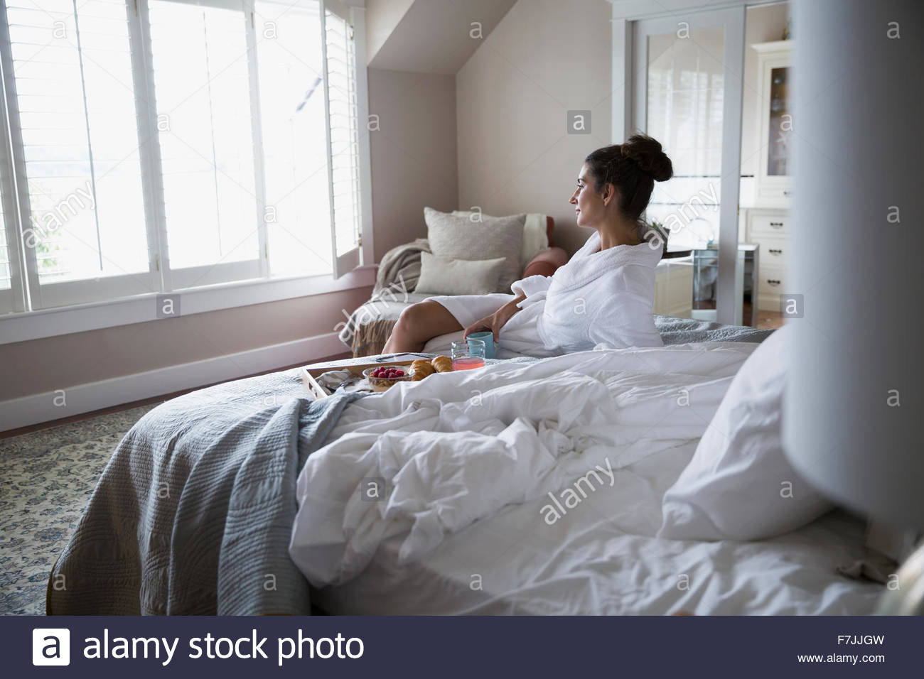 Donna in accappatoio gustando la prima colazione a letto Immagini Stock