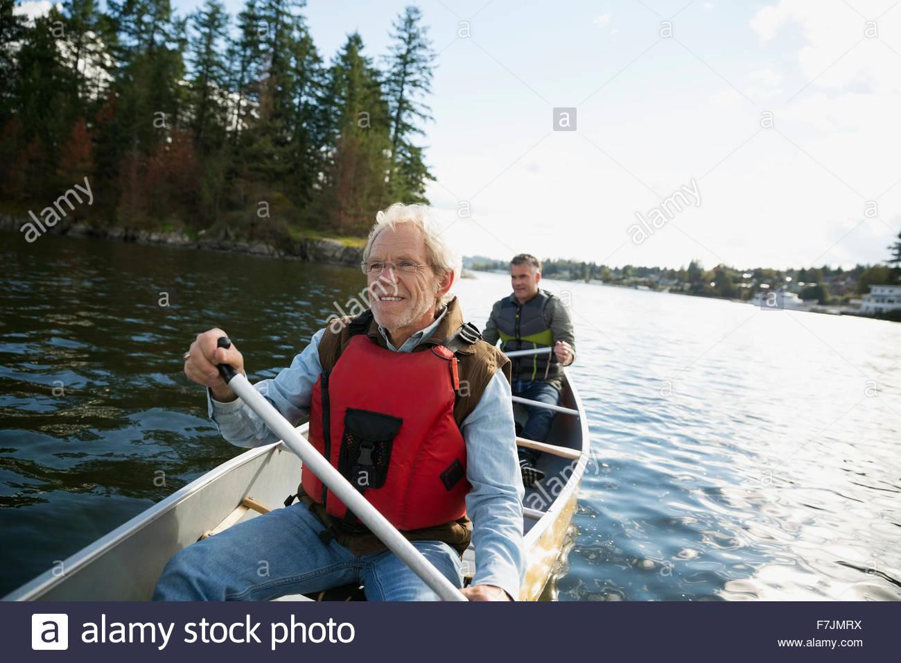 Padre e figlio in canoa sul lago Immagini Stock