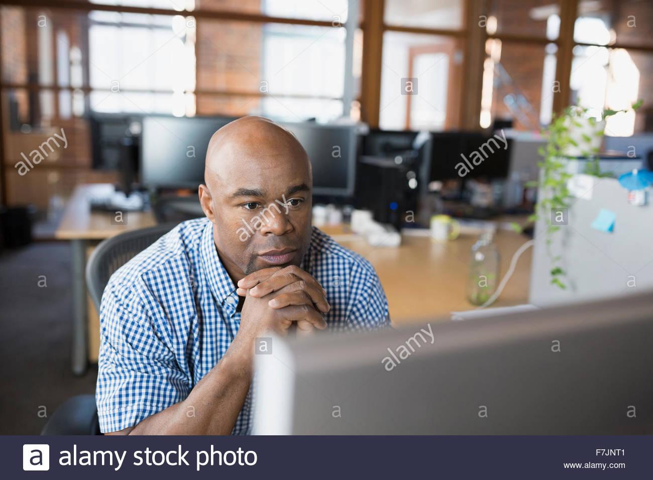 Imprenditore serio lavora al computer in ufficio Immagini Stock