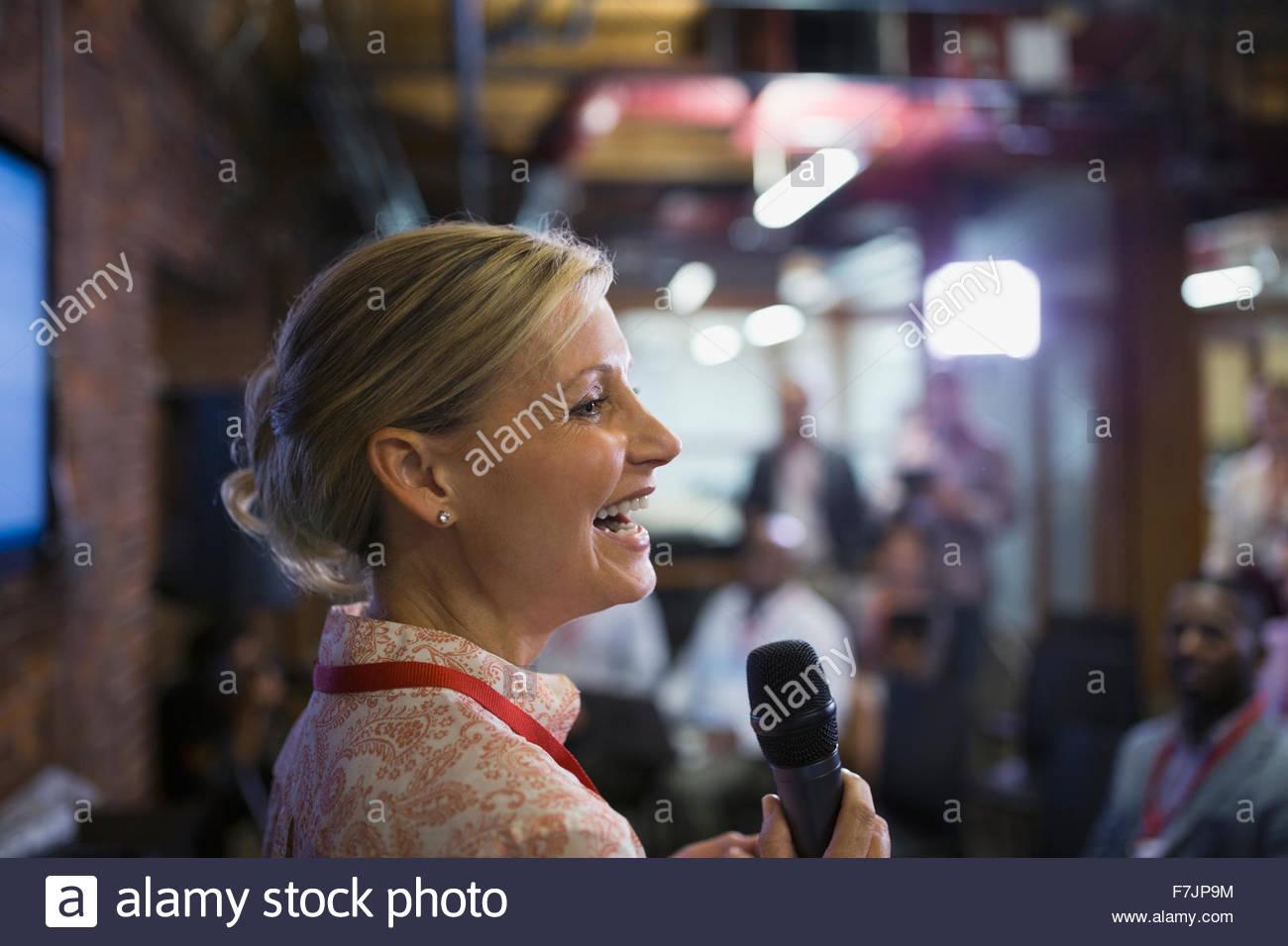 Close up imprenditrice con microfono intervenendo a una conferenza Immagini Stock