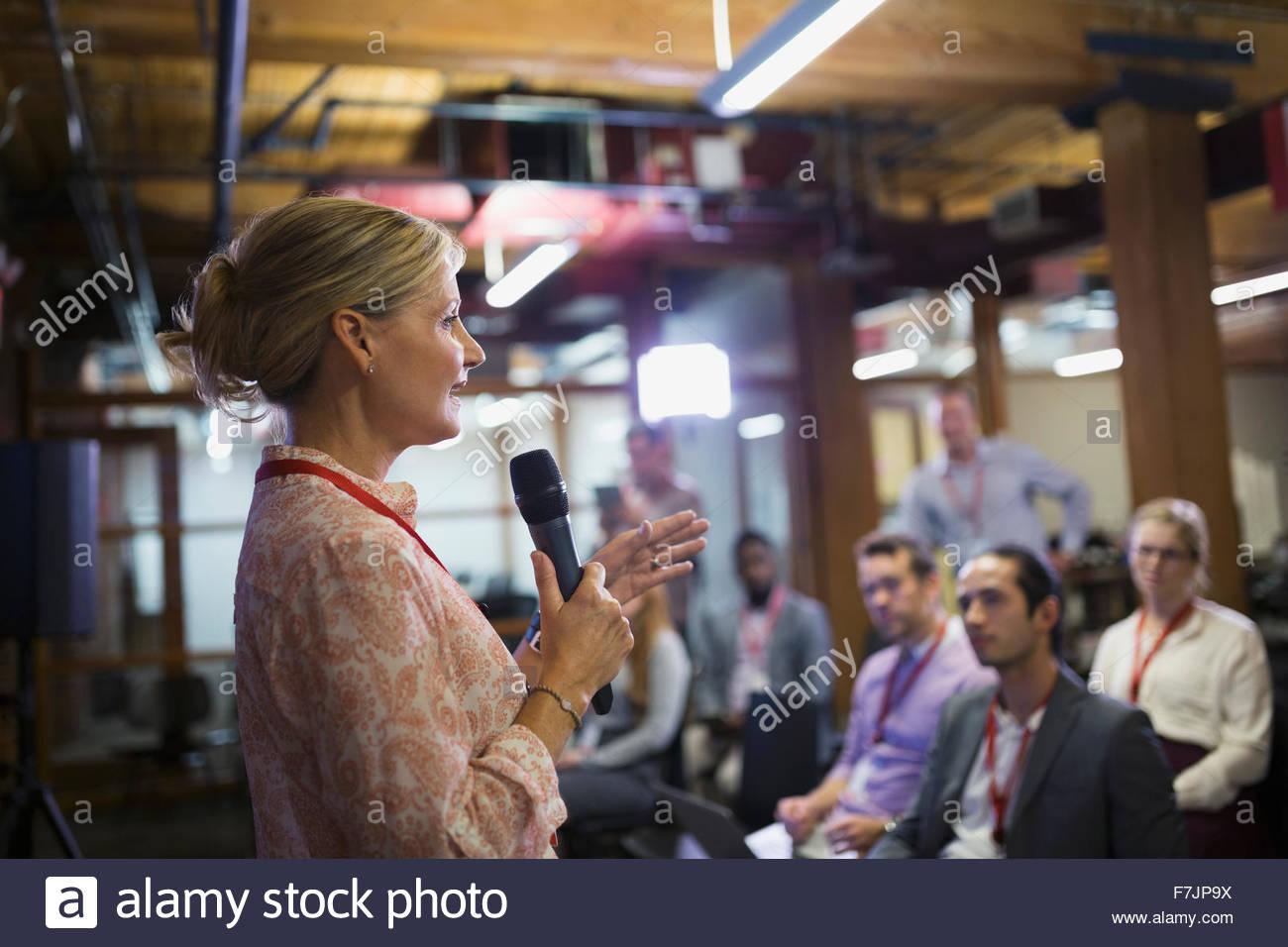Imprenditrice con microfono parlando al Convegno pubblico Immagini Stock