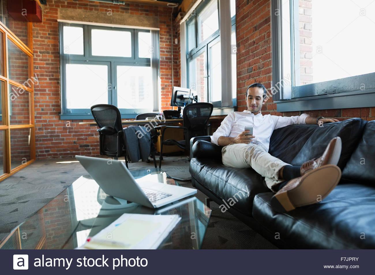 Imprenditore confortevole texting sul divano per ufficio Immagini Stock