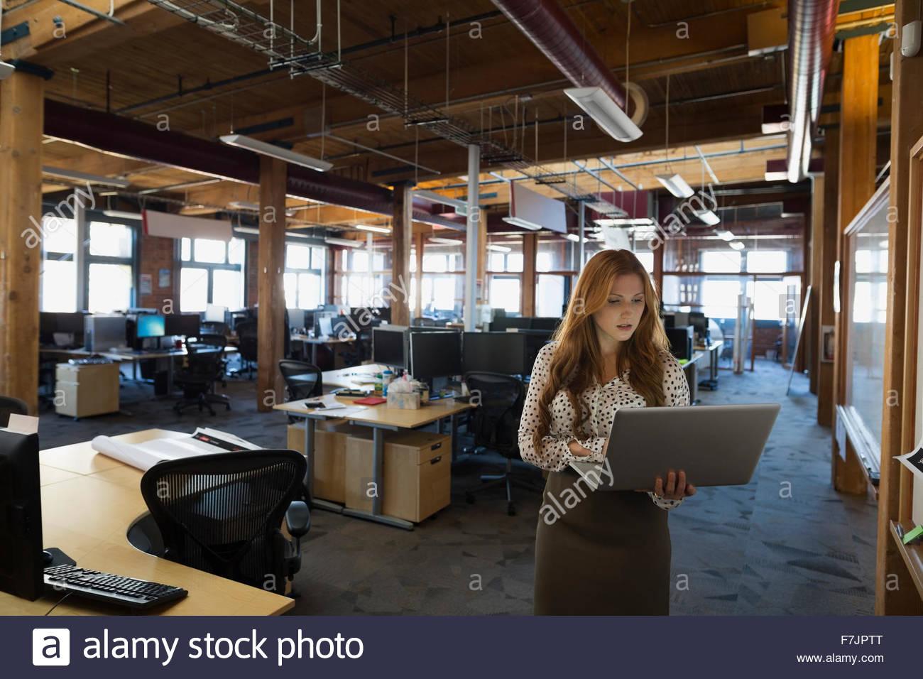 Imprenditrice utilizzando computer portatile in ufficio Immagini Stock