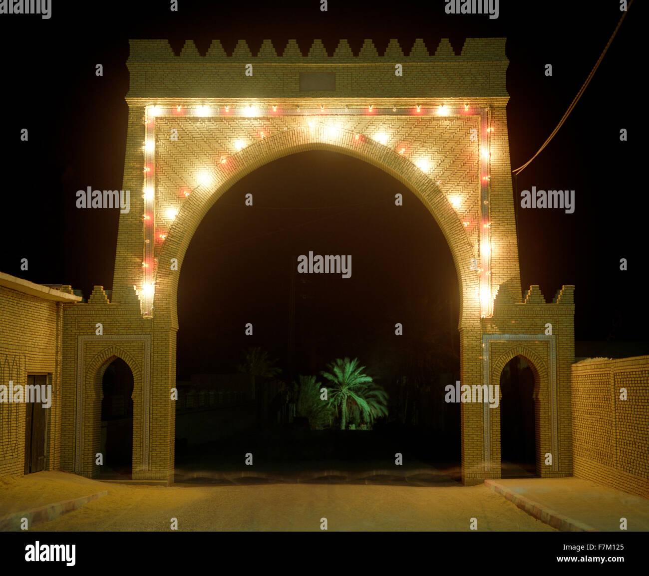 Una porta illuminata di notte conduce alla principale Palmeraie in Tozeur. Un albero di palma è illuminato Immagini Stock