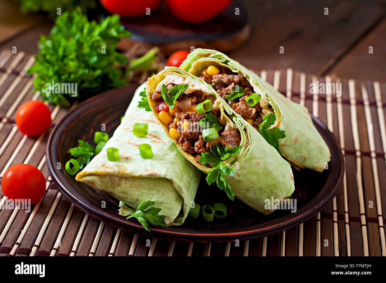 Burrito si avvolge con carne macinata e verdure su un sfondo di legno Immagini Stock