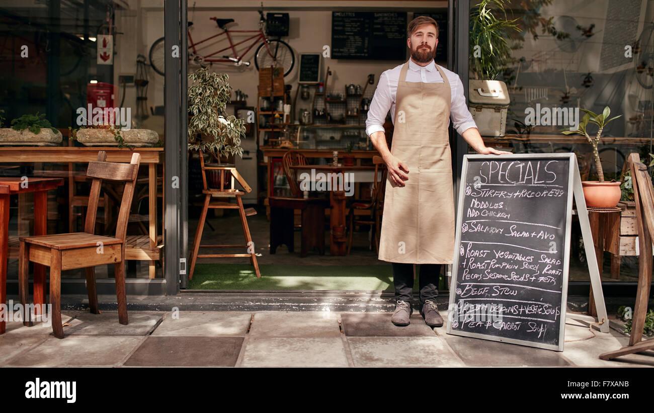 Ritratto di giovane uomo in piedi all'ingresso della sua caffetteria con un bordo nero. Barista in piedi la Immagini Stock