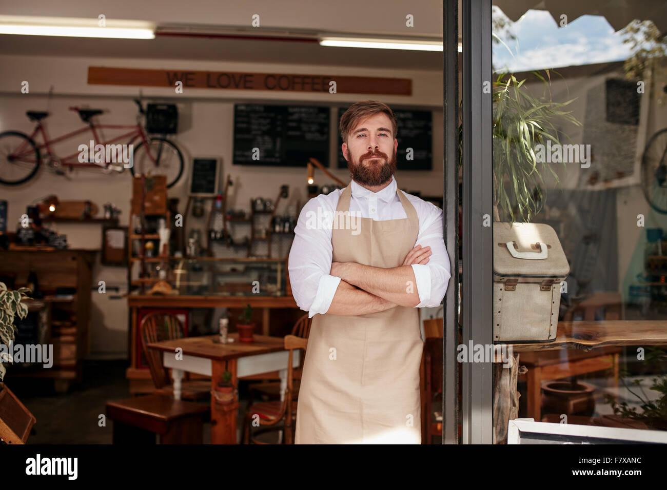 Colpo di cafe proprietario orgogliosamente in piedi nel vano della porta del suo ristorante. Giovane uomo che indossa Immagini Stock