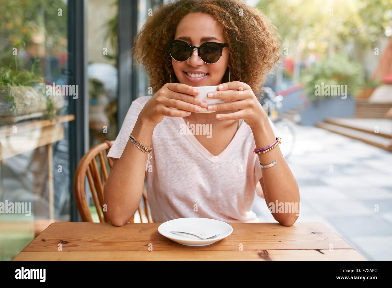 Ritratto di ragazza giovane e carina di bere il caffè. Giovane donna africana tenendo una tazza di caffè Immagini Stock