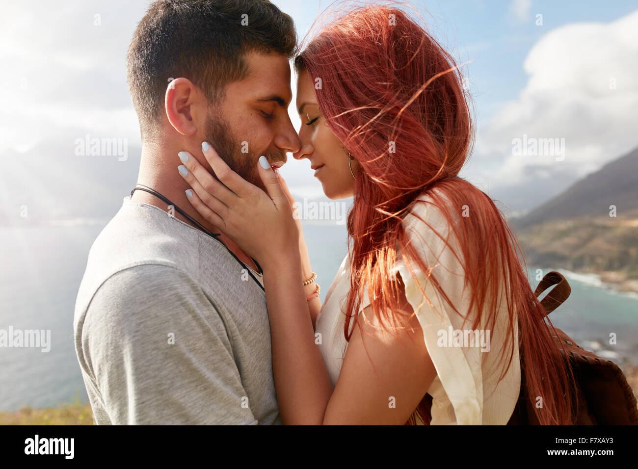 Ritratto di affettuosa coppia giovane circa a kiss. Romantico giovane uomo e donna la condivisione di un bel momento Immagini Stock