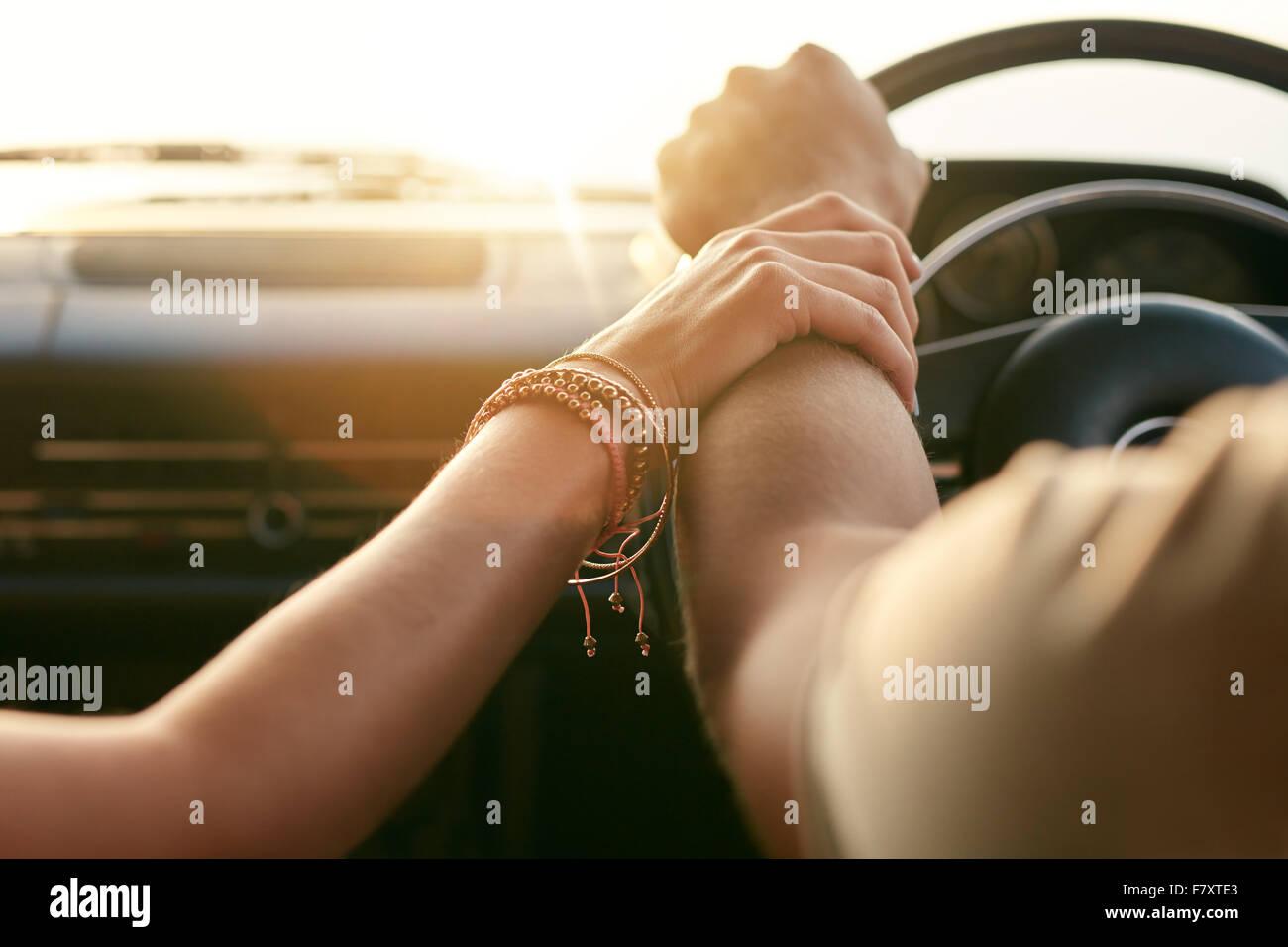 Immagine ravvicinata di amare giovane che viaggiano in auto e tenendo le mani. Focus sulle mani di un uomo e di Immagini Stock