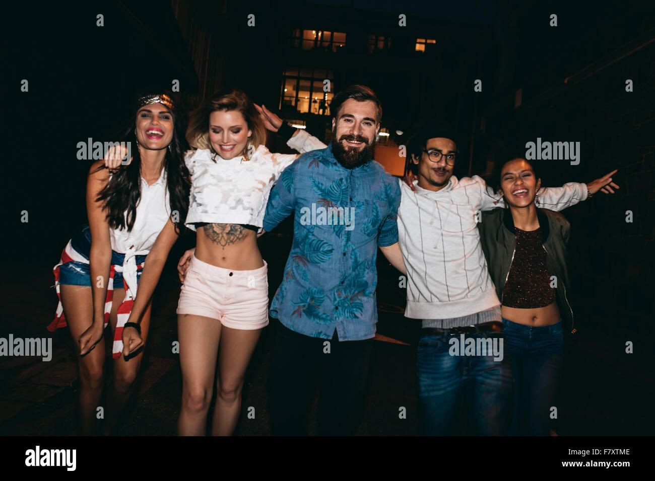 Ritratto di gruppo di amici di partito, insieme all'esterno. Multirazziale giovani appendere fuori la sera. Foto Stock