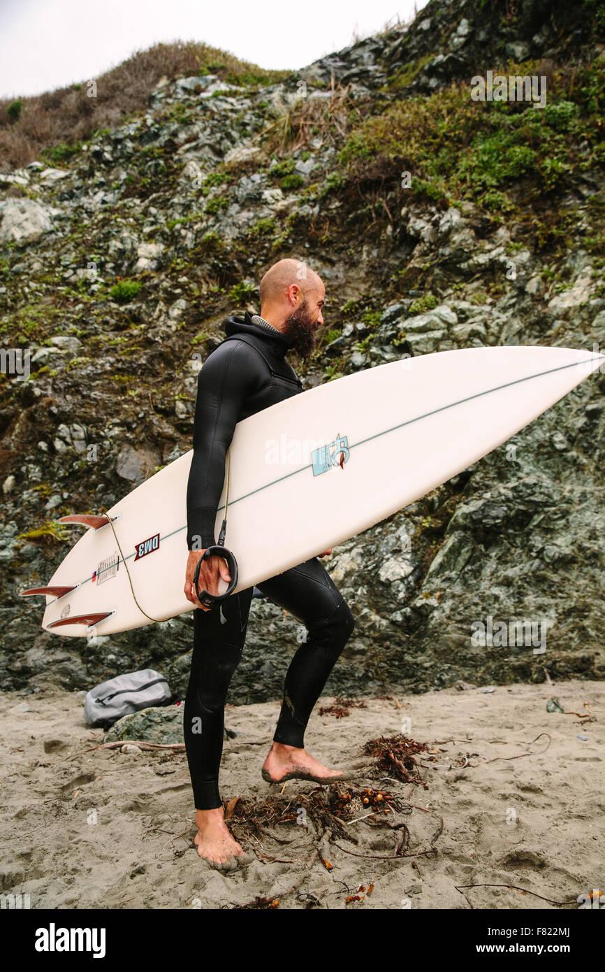 Un surfista proviene dall'acqua su una spiaggia di Big Sur, California. Immagini Stock