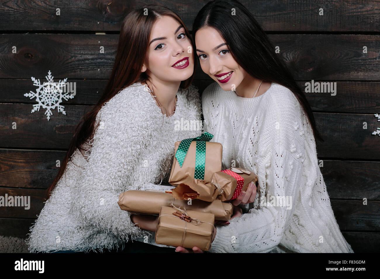 Due belle ragazze offrono doni alla fotocamera Immagini Stock