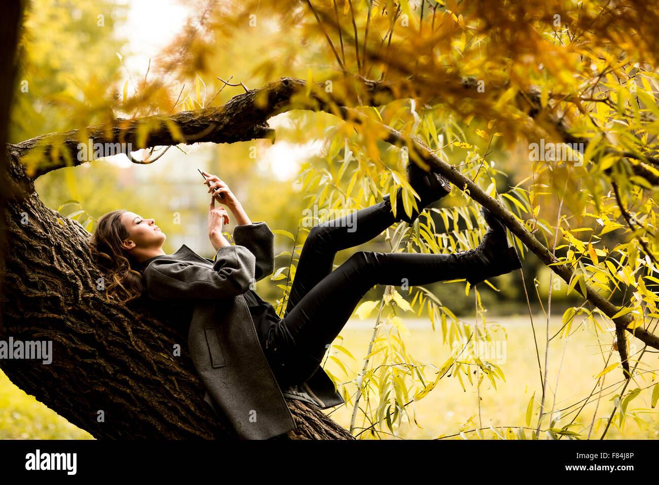Oung donna in appoggio sulla struttura ad albero con il telefono cellulare Immagini Stock