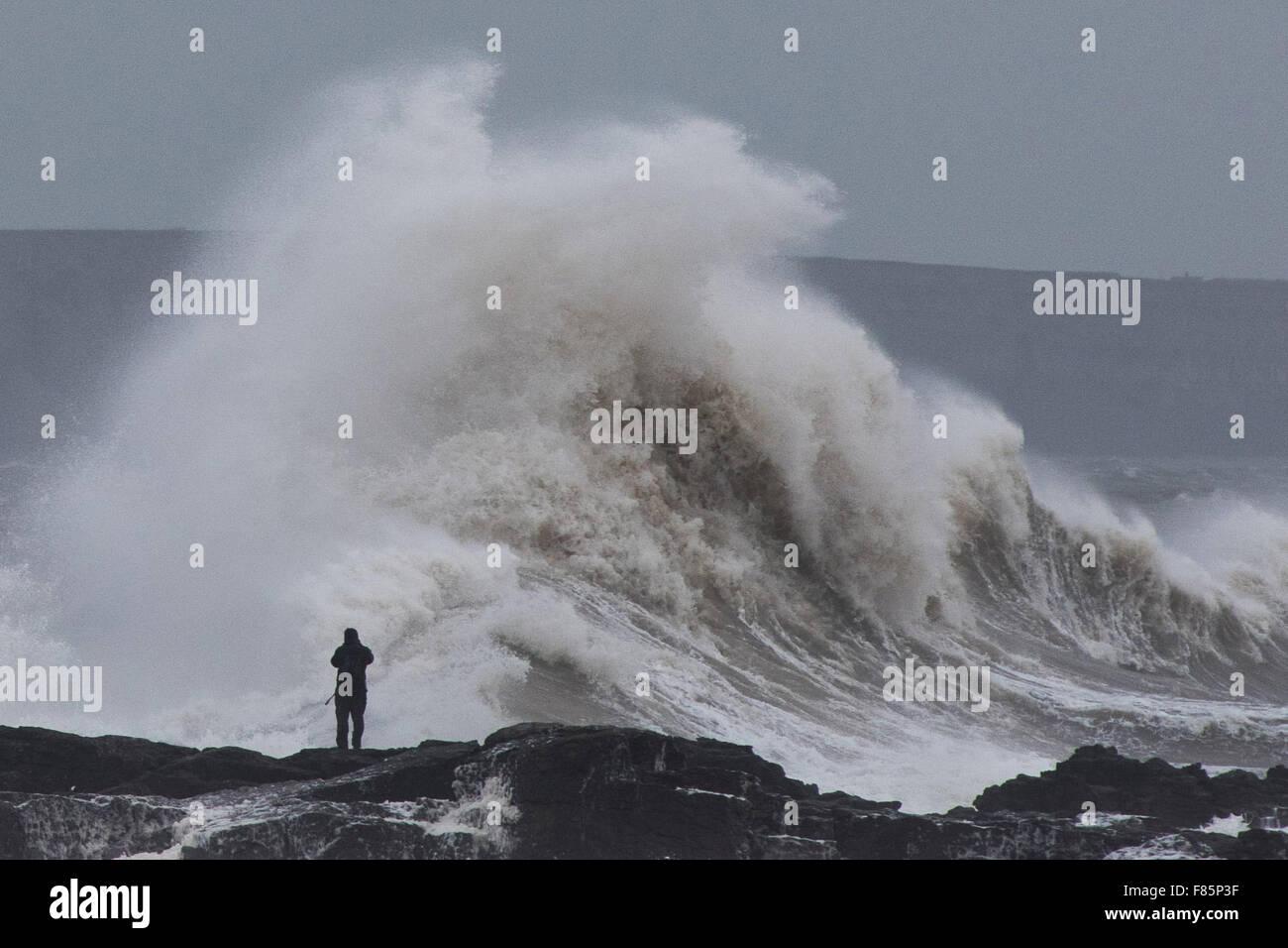 Porthcawl, Wales, Regno Unito. Il 5 dicembre 2015. Un fotografo sta pericolosamente vicino al mare in Porthcawl, Immagini Stock