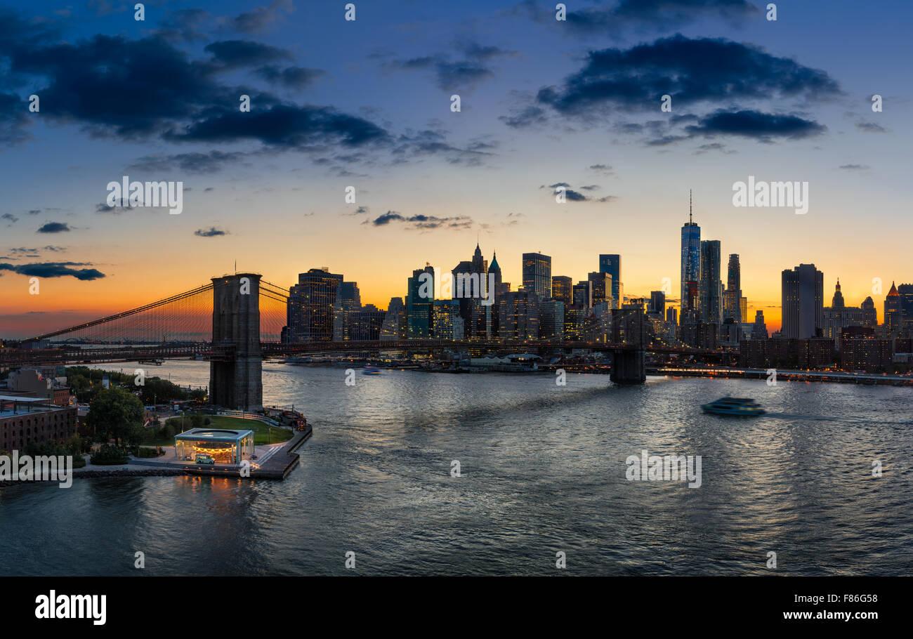 Vista in elevazione del Ponte di Brooklyn, East River, Lower Manhattan, grattacieli e nuvole al tramonto. La città Immagini Stock