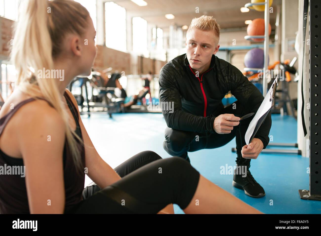 Giovane donna in una palestra seduto sul pavimento e parlando con il suo allenatore privato su un programma di esercizi Immagini Stock