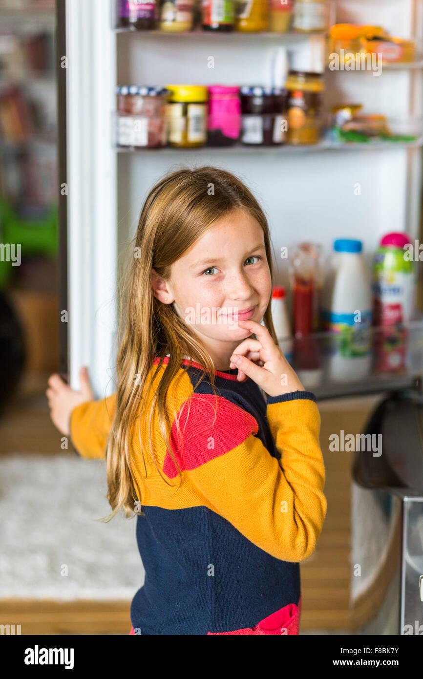 8 anno vecchio ragazzo davanti a un frigorifero. Immagini Stock