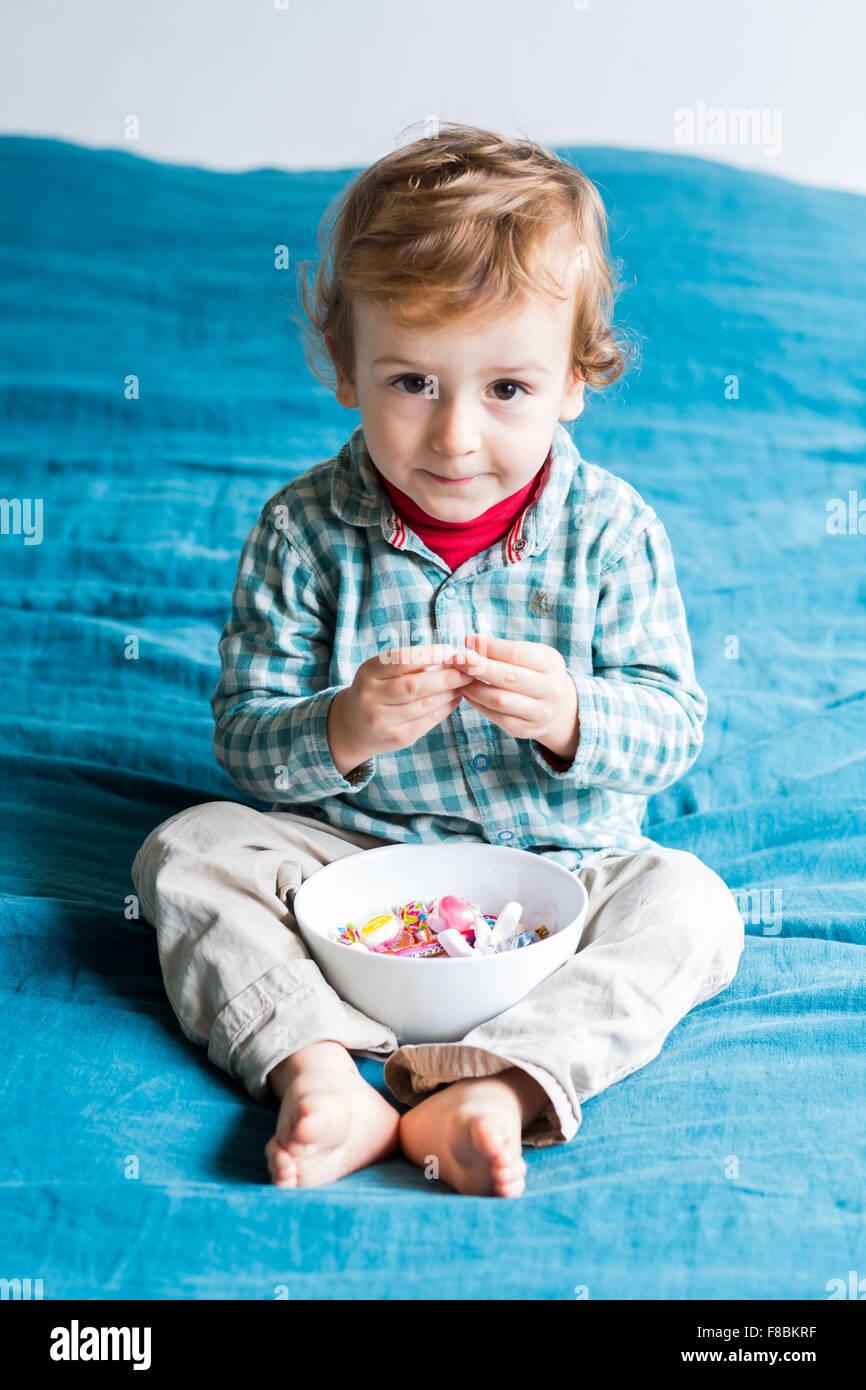 2 anno-vecchio ragazzo mangiando caramelle zuccherine. Immagini Stock