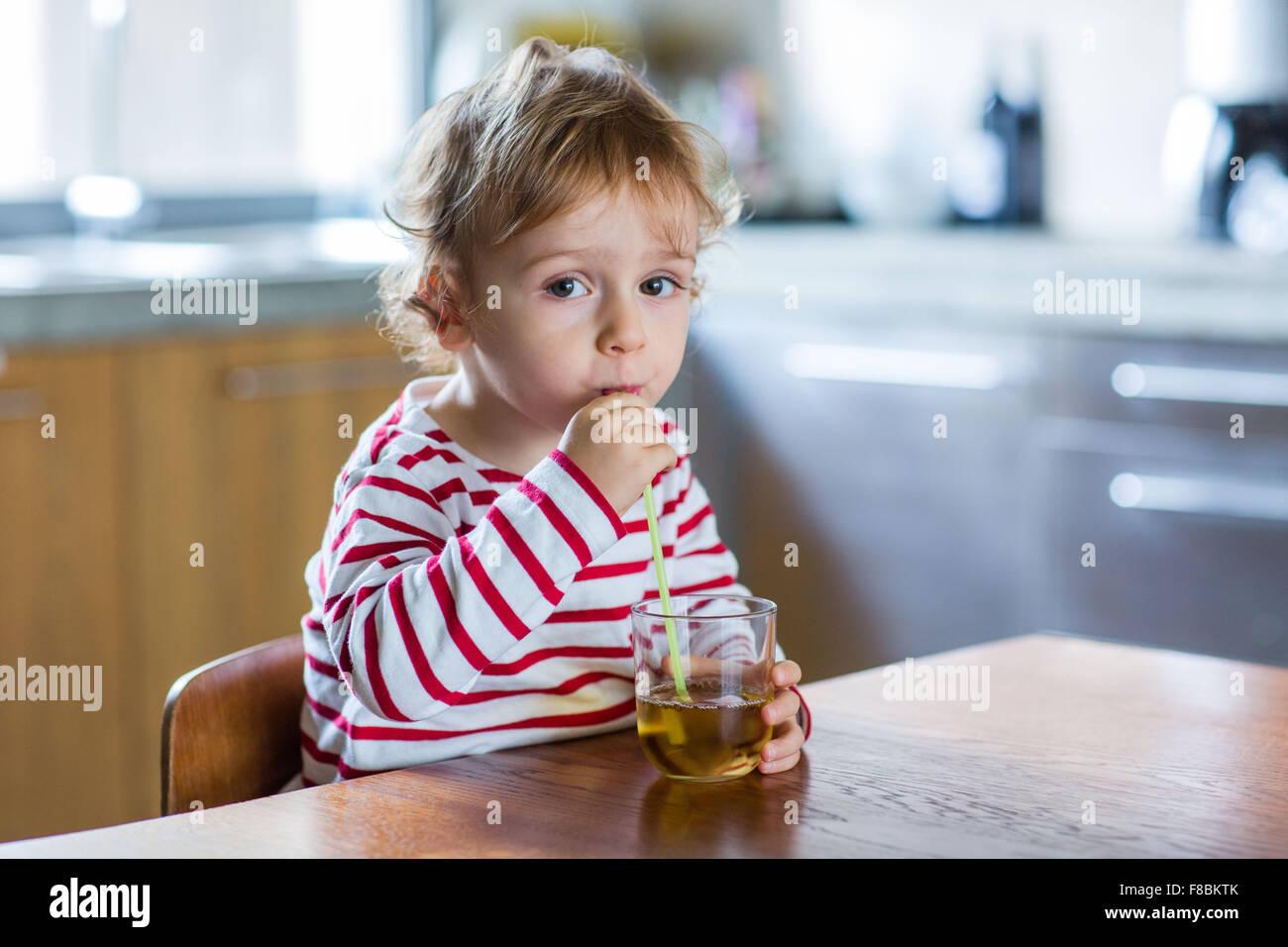 2 anno-vecchio ragazzo di bere succo di frutta. Immagini Stock