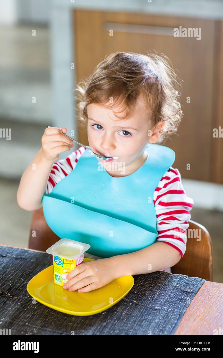 2 anno-vecchio ragazzo di mangiare uno yogurt. Immagini Stock