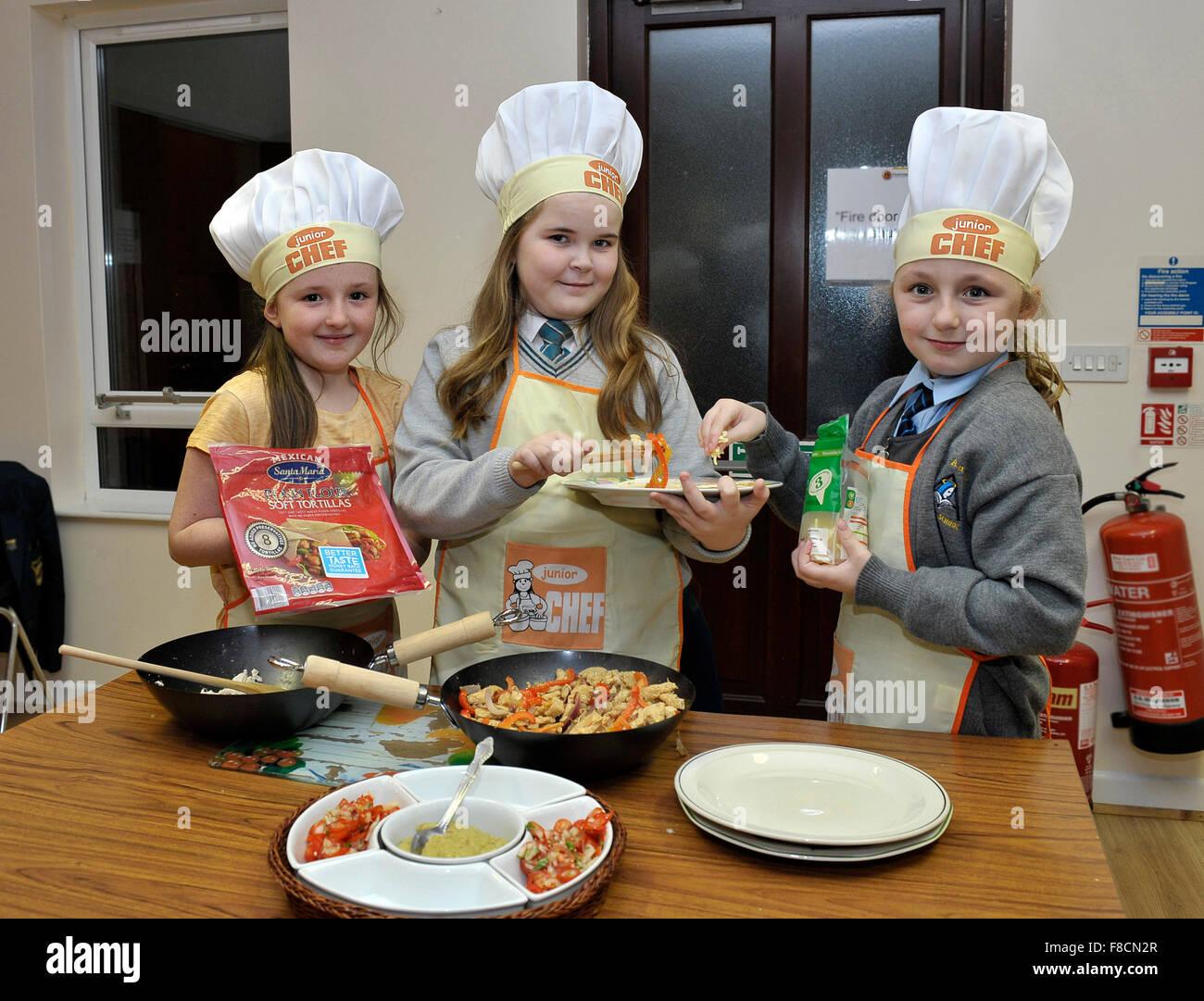 Irish gli allievi della scuola primaria vestito come junior chef. Foto Stock