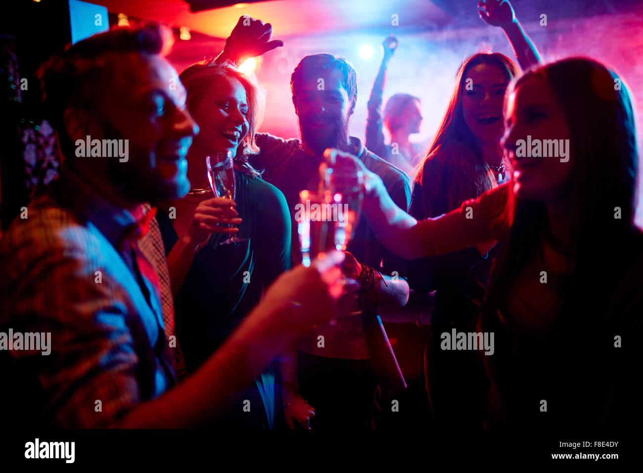 Un gruppo di giovani che celebra con bevande in discoteca Immagini Stock