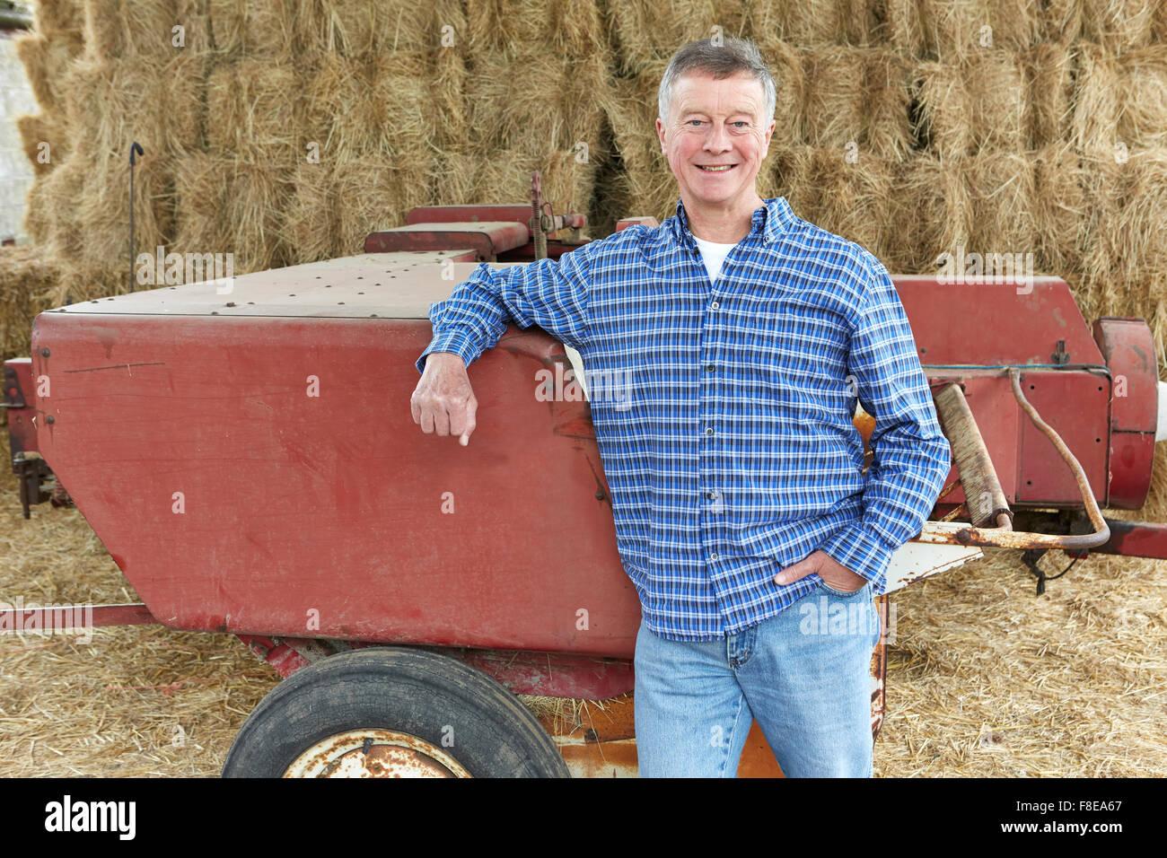 Agricoltore in piedi di fronte a balle e le vecchie attrezzature agricole Immagini Stock