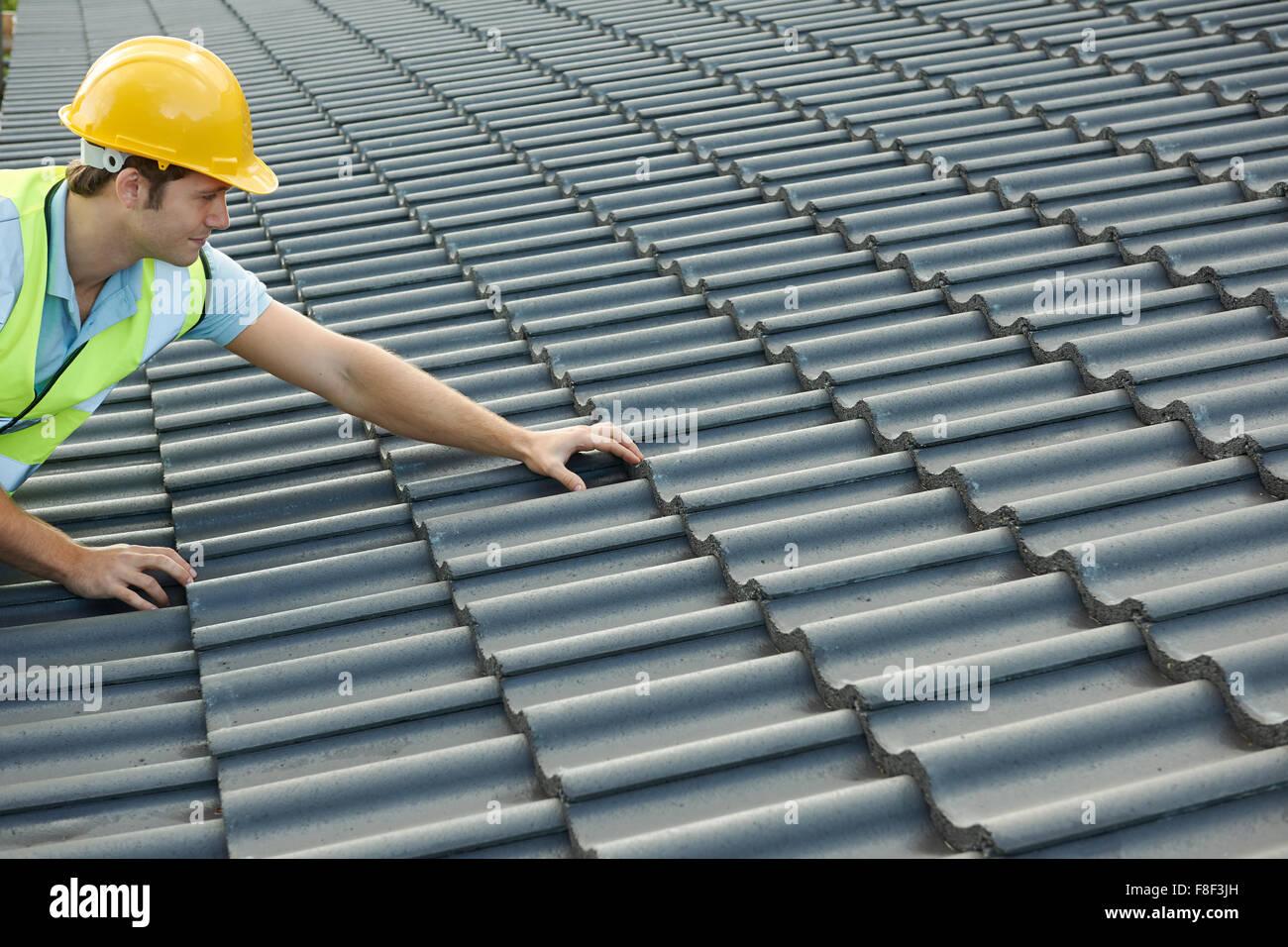 Builder lavorando sul tetto del nuovo edificio Immagini Stock