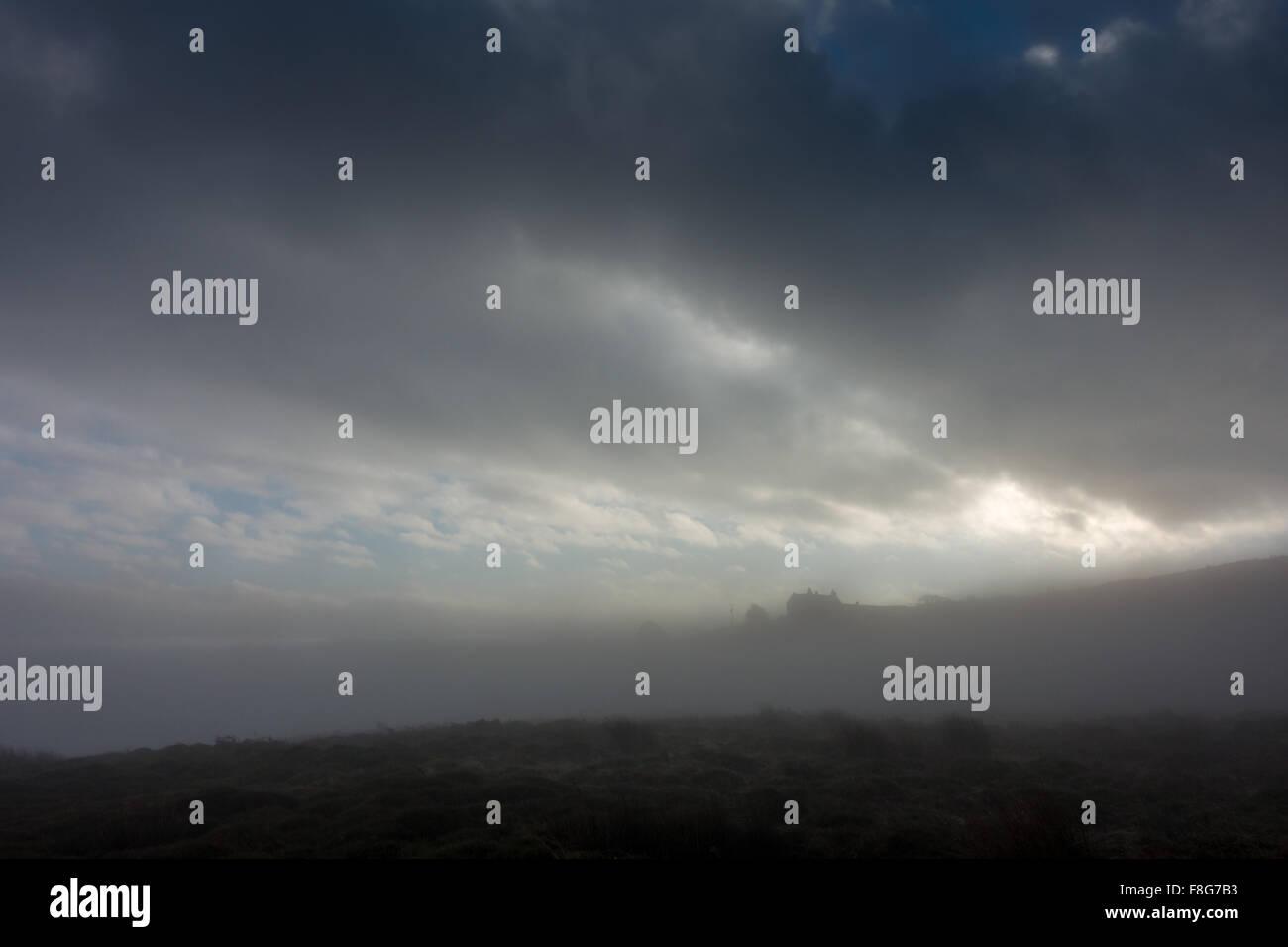 Inversione di Cloud dà una sensazione inquietante di Mori con una casa in alto sulla collina immersa nella foschia Foto Stock