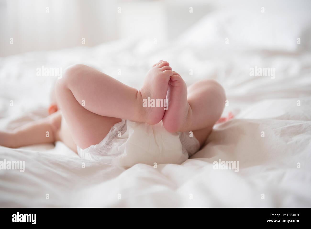 Gambe di soggetti di razza caucasica bambina posa sul letto Foto Stock