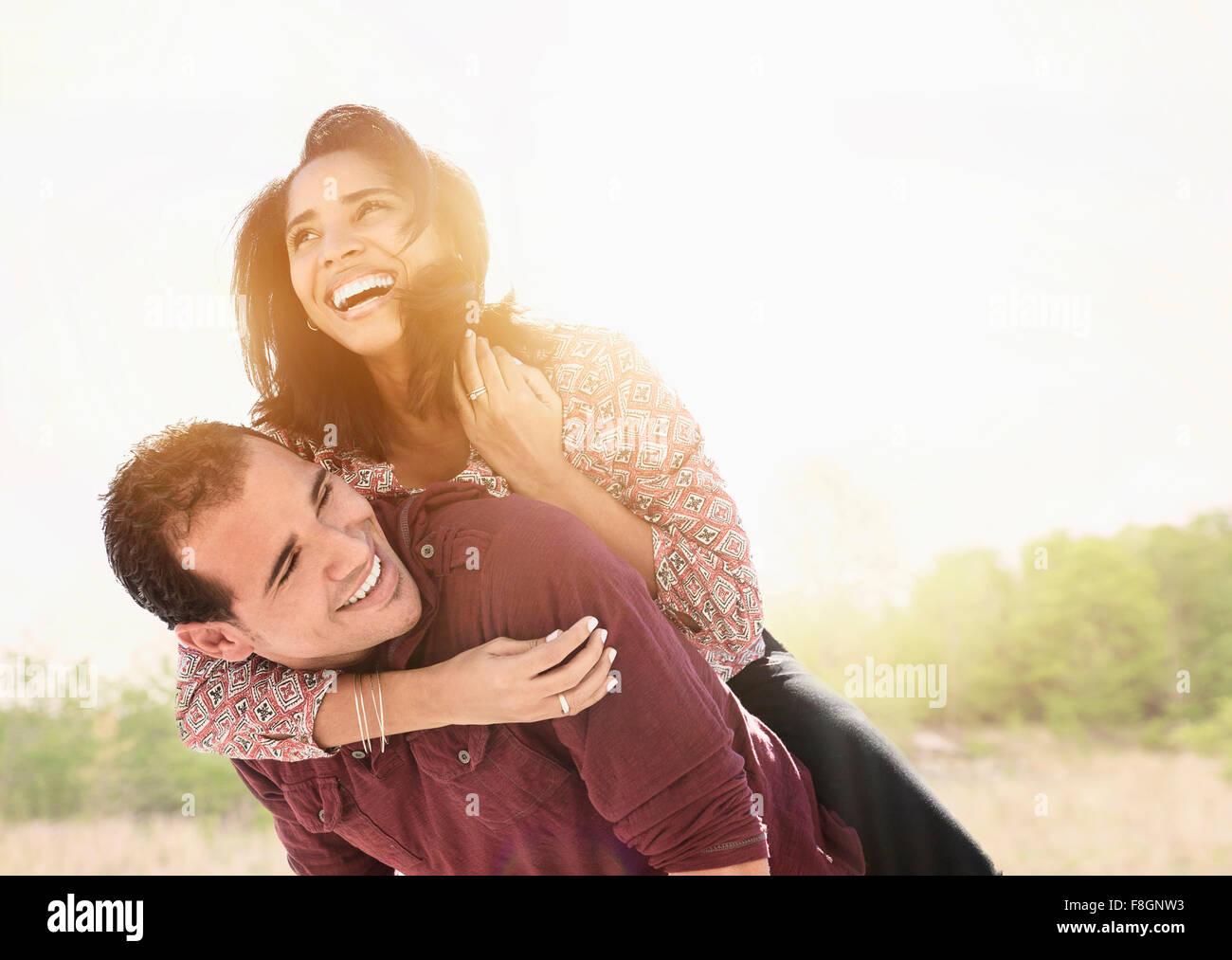 Uomo ispanico che trasportano ragazza piggyback Foto Stock