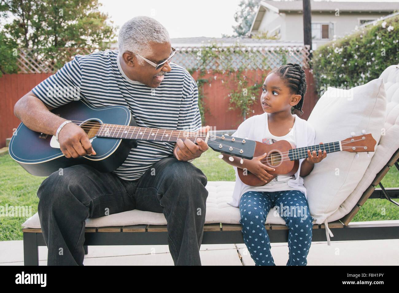 African American nonno nipote di insegnare a suonare la chitarra Foto Stock