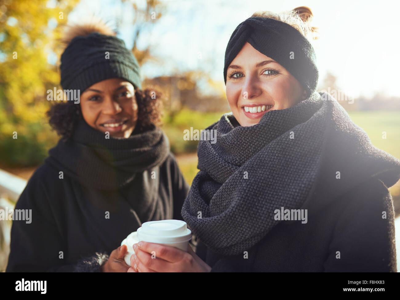 Due amiche guardando la fotocamera e sorridenti mentre si tiene il caffè per andare Immagini Stock