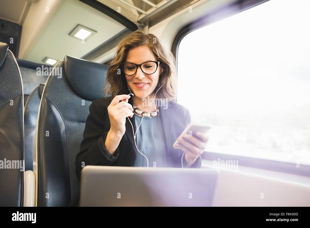 Metà donna adulta sul treno, tenendo lo smartphone, guardando il computer portatile Immagini Stock