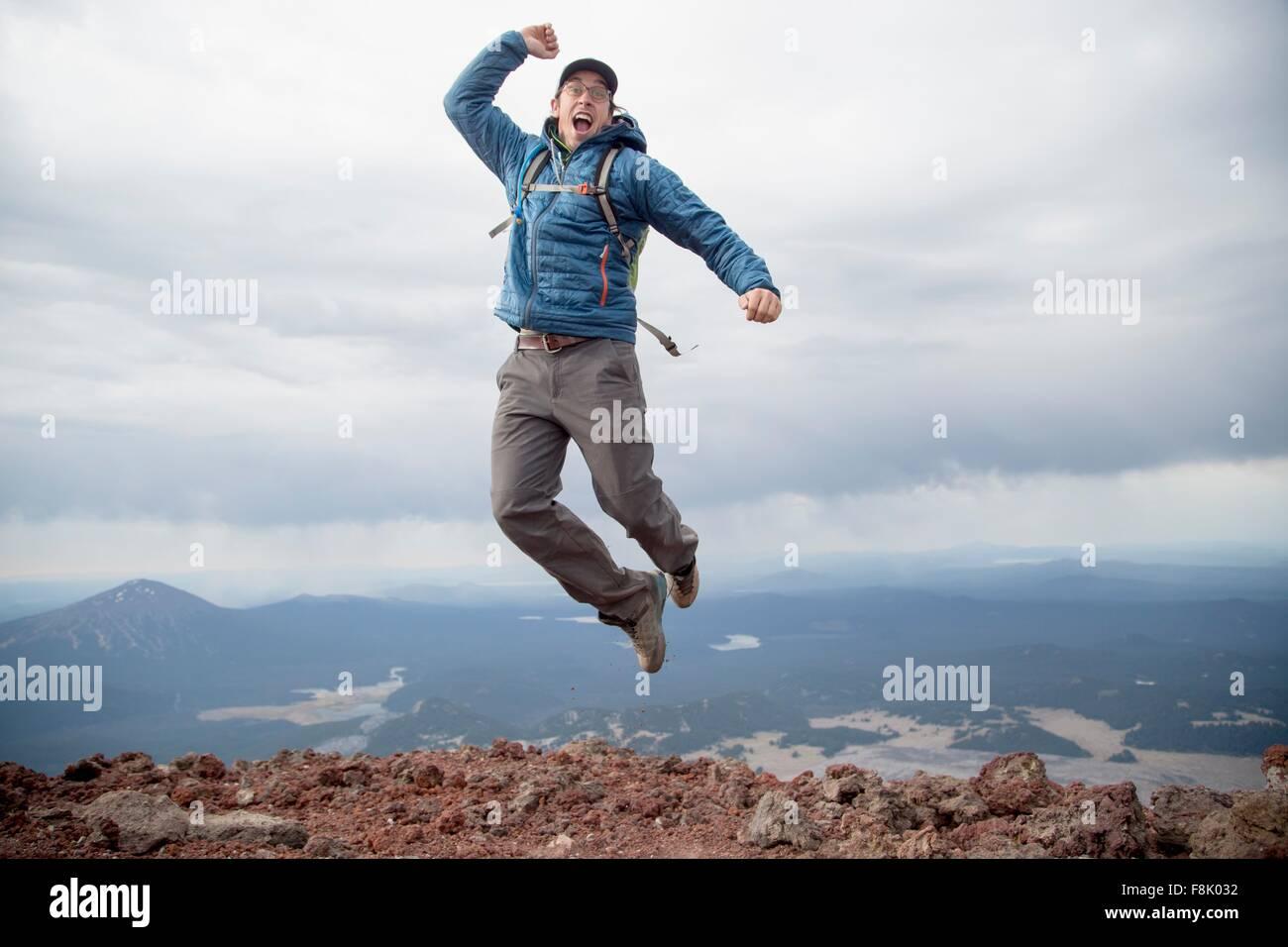 Giovane uomo salti di gioia al vertice del Sud Suor vulcano, piegare, Oregon, Stati Uniti d'America Immagini Stock