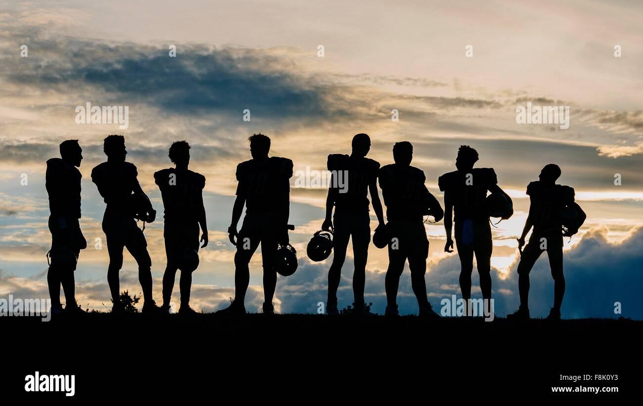 Silhouette di un gruppo di giovani american football giocatori, in piedi in fila Immagini Stock