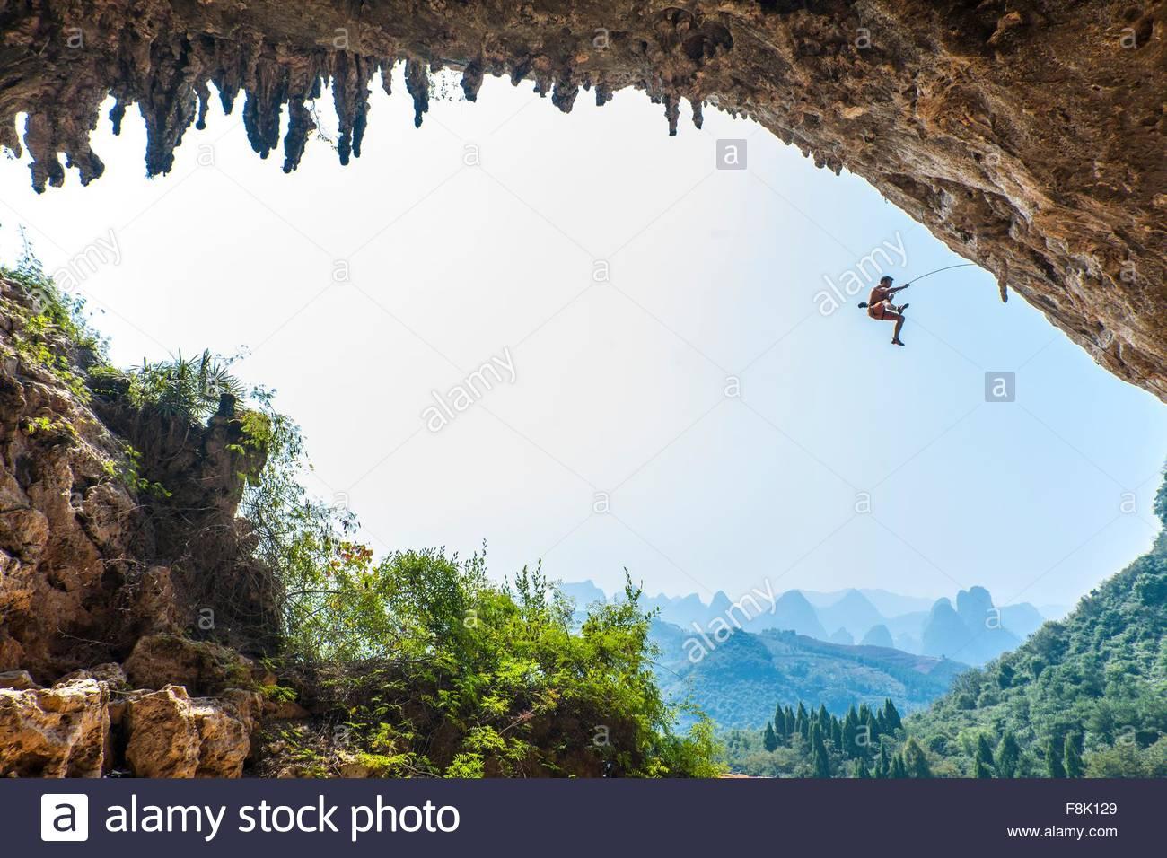 Scalatore maschio tenendo una caduta a Odin Den accanto alla collina della Luna in Yangshuo, Guangxi Zhuang, Cina Immagini Stock